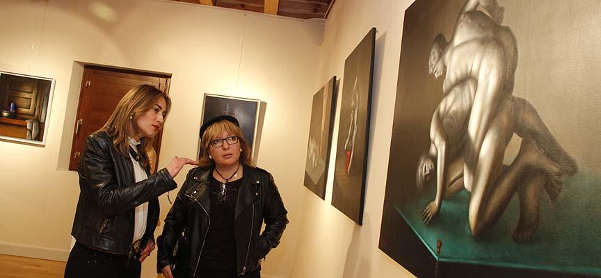 La pintora Virginia Villar (izquierda) explica su obra a la concejala de Cultura.