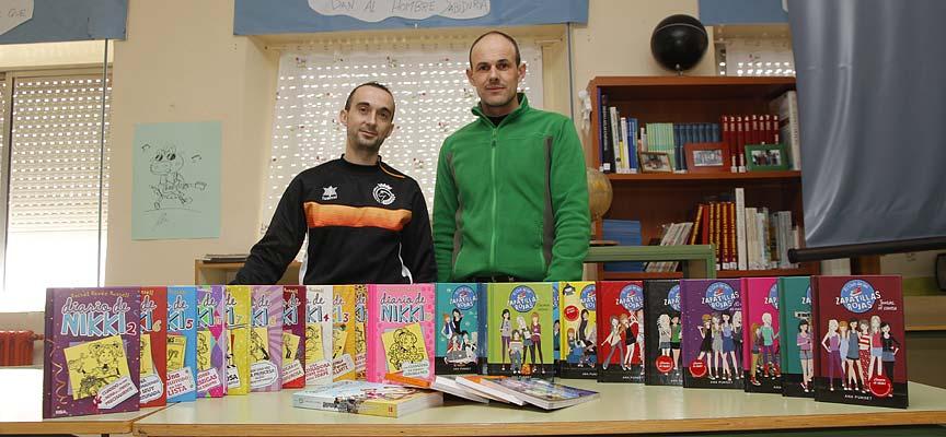 El presidente del Racing Cuéllar, Jesús Ferreiro (izquierda) entrega los libros al director del colegio La Villa, Álvaro Catalina.