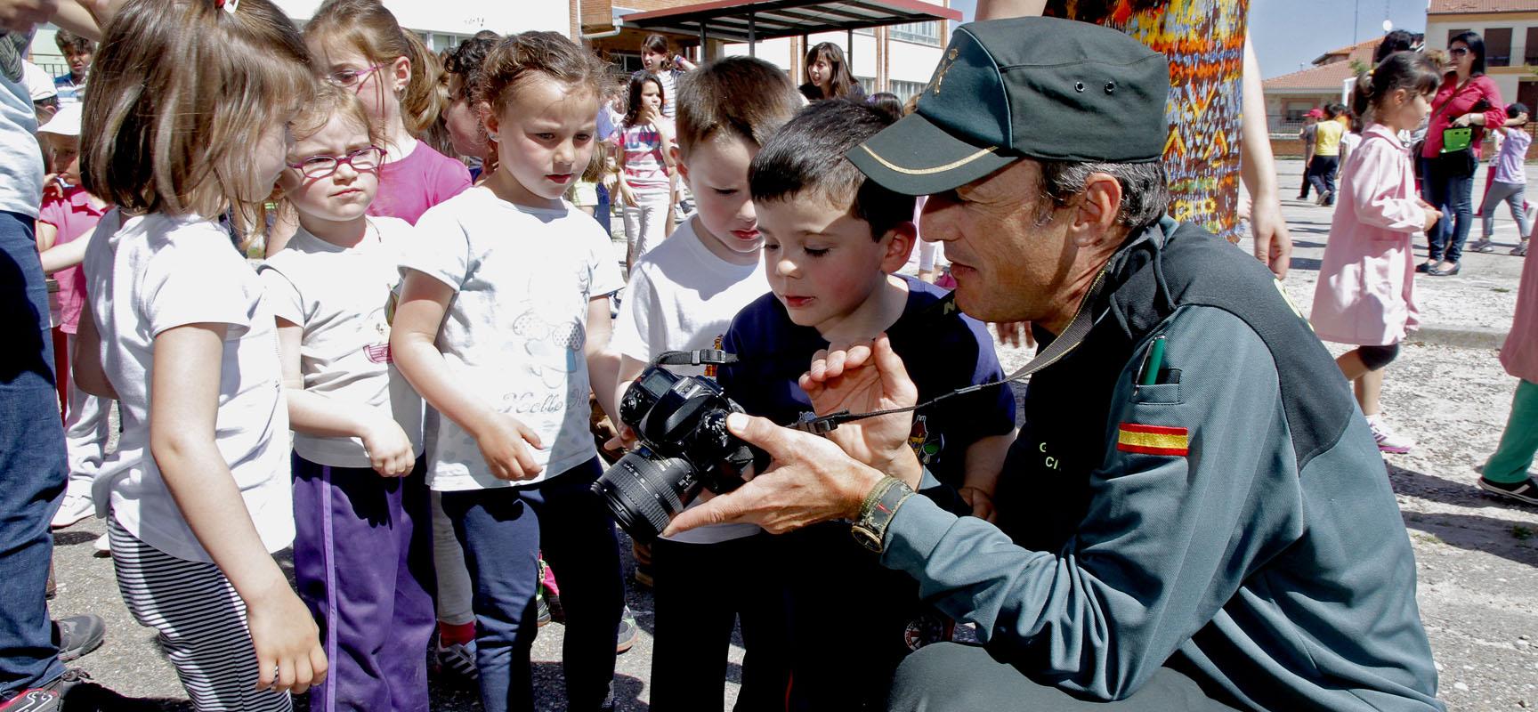 Un agente muestra a los niños las imágenes tomadas con su cámara.||Foto: Gabriel Gómez||.