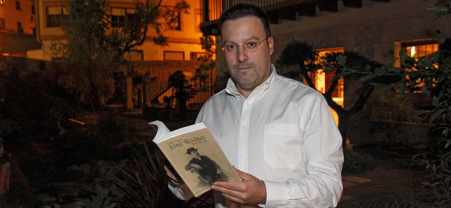 Carlos Álvaro junto a su libro sobre Rodao tras la presentación.