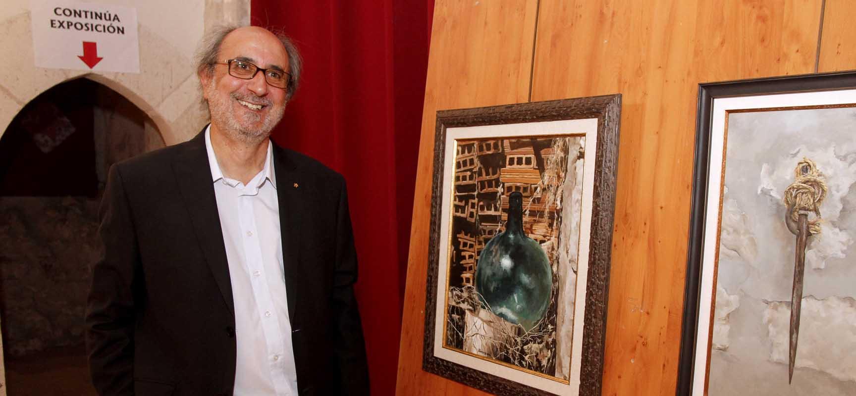 José Luis Llorente junto al cuadro de una garrafa que encontró en el patio de la iglesia de La Cuesta.