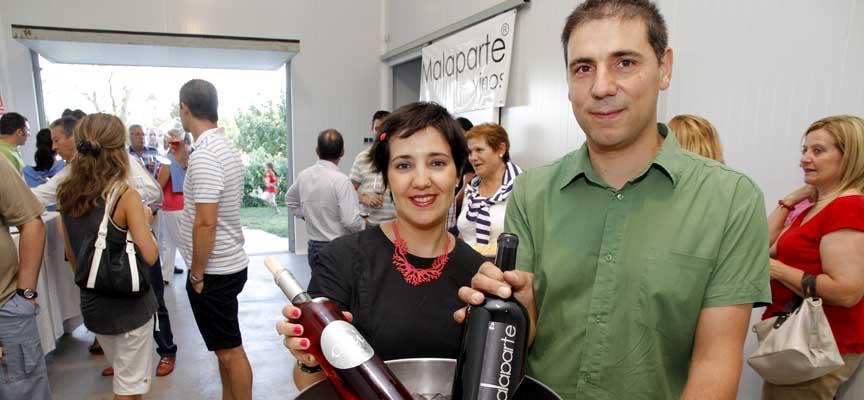Elisa de Frutos y Rubén Salamanca muestran en su bodega dos de las variedades de vino que elaboran.