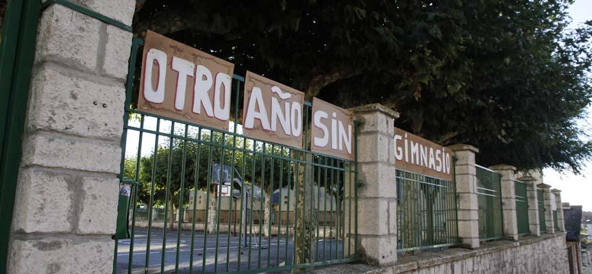 Rótulo en la valla exterior del colegio La Villa recordando la ausencia de un gimnasio en el centro.