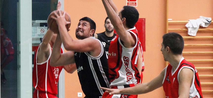 """Un jugador del Baloncesto Cuéllar """"A"""" intenta encestar ante la presión de la defensa rival."""