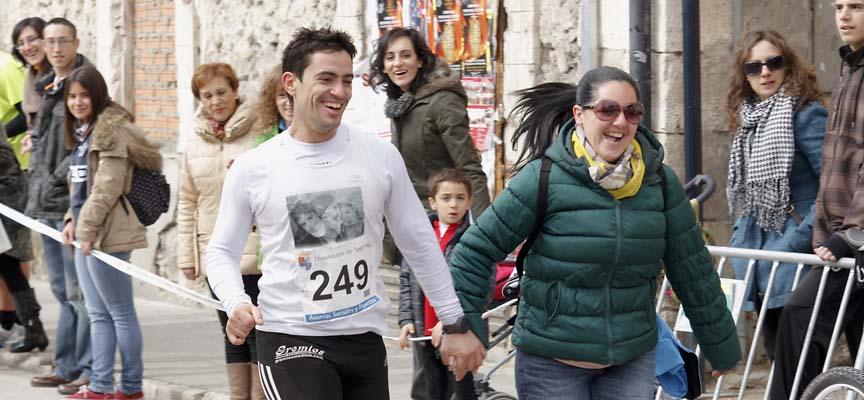 Una mujer acompaña a un corredor en los últimos metros de la Carrera de las Murallas de 2013.