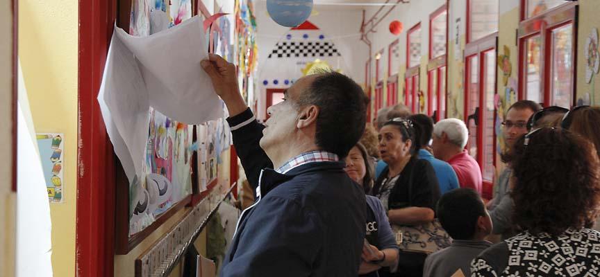 Un votante consulta las listas en el colegio electoral.