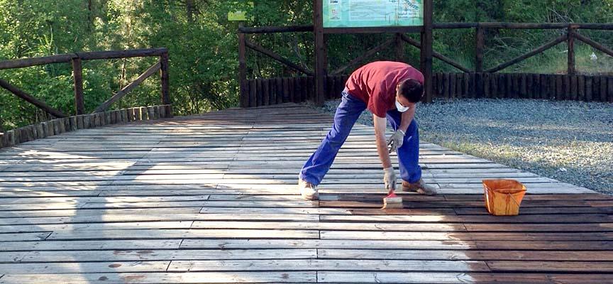 Un operario municipal pintando la madera del inicio de la Senda