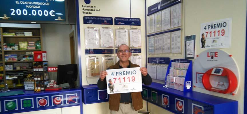 Ángel Sacristán muestra el cartel con el número premiado vendido en su administración.