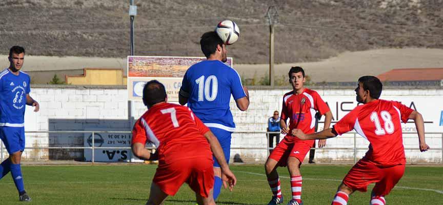 Pablo Lozano cabecea el balón ante la oposición de varios jugadores rivales.