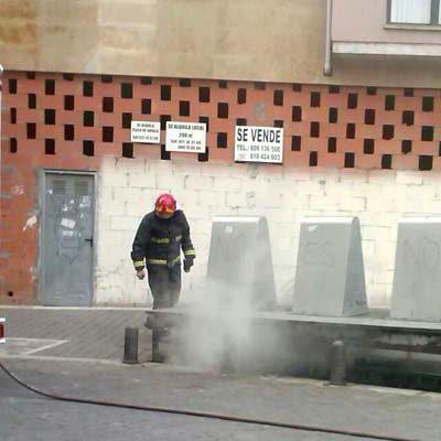 Los bomberos sofocan el incendio en unos contenedores en la calle Resina