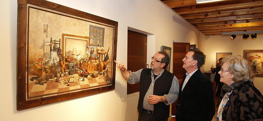 Ricardo Renedo (izquierda) explica una de sus obras a visitantes de su exposición en Tenerías.
