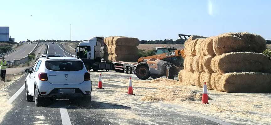 Corte al tráfico de la A-601 al perder su carga un camión de pacas